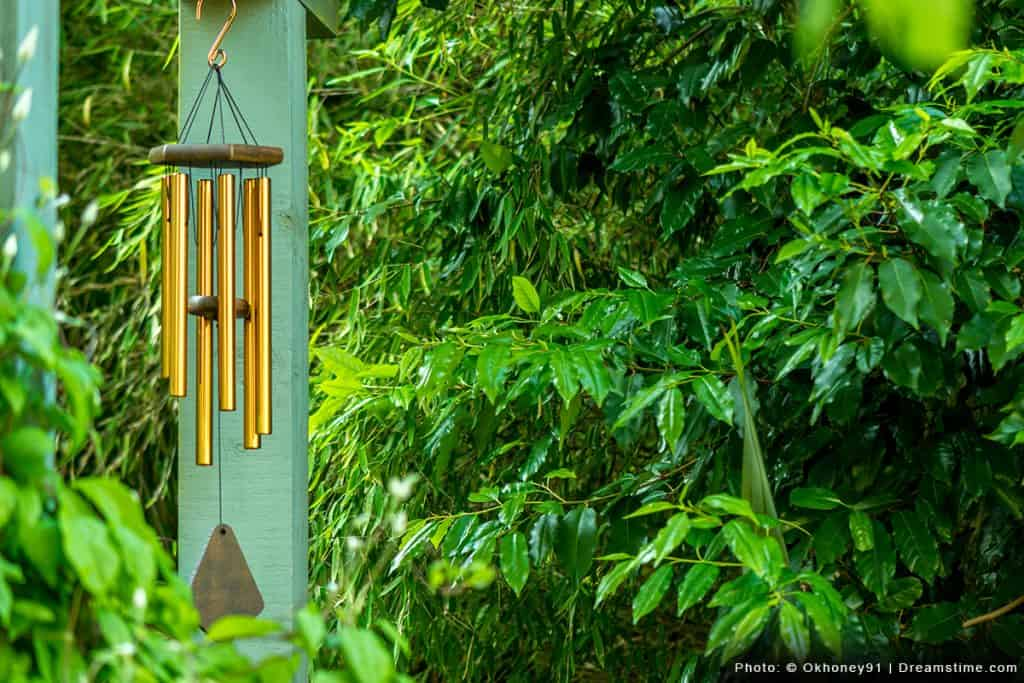 Wind chimes on post with grass background
