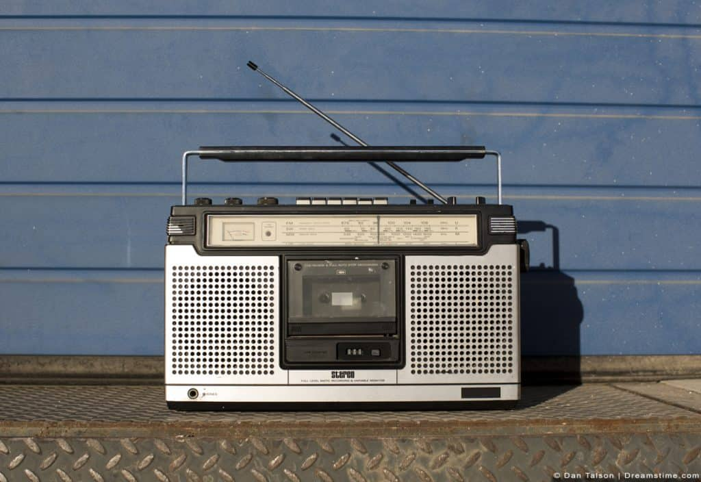 Old Radio Outside On Metal Against Blue Wall