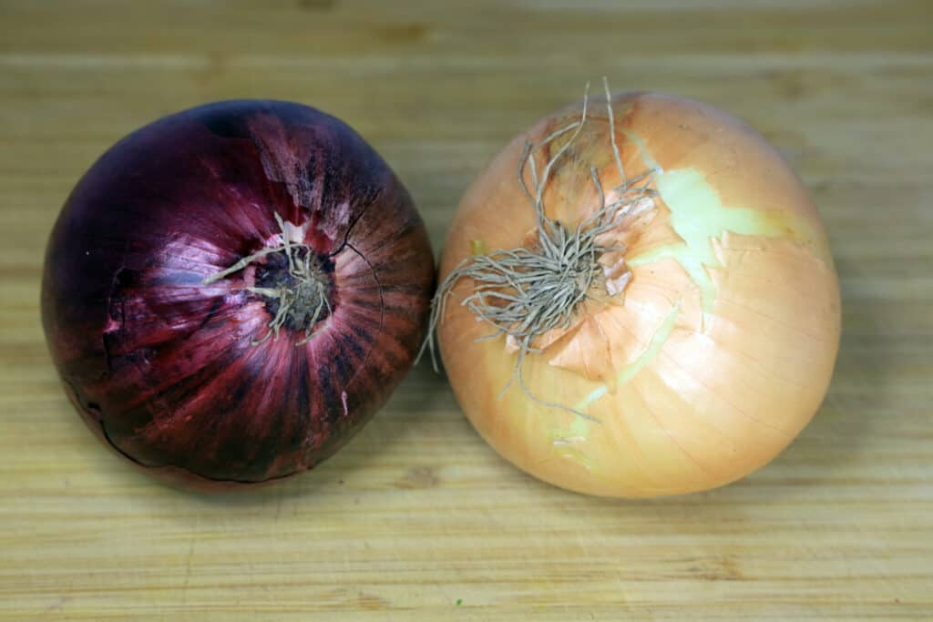 A view looking down on a group of onions on a worn butcher block cutting board.